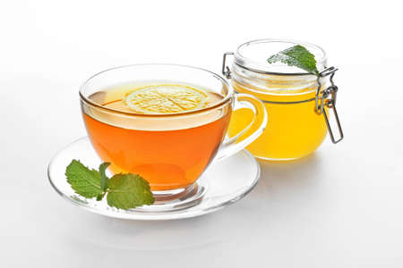 Glass cup of tasty tea with honey, mint and lemon on white background