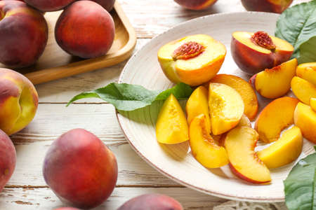 Plate with tasty peaches on white table Standard-Bild