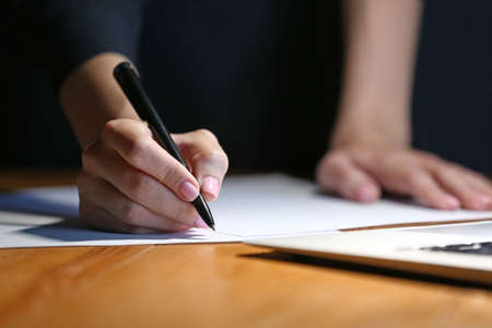Woman writing something on sheet of paper at workplace in evening, closeup