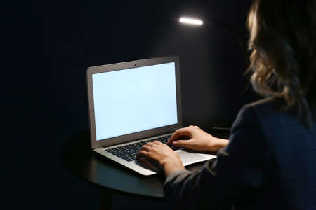 Woman working on laptop at table in evening