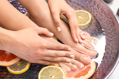 Young woman undergoing spa pedicure treatment in beauty salon, closeup