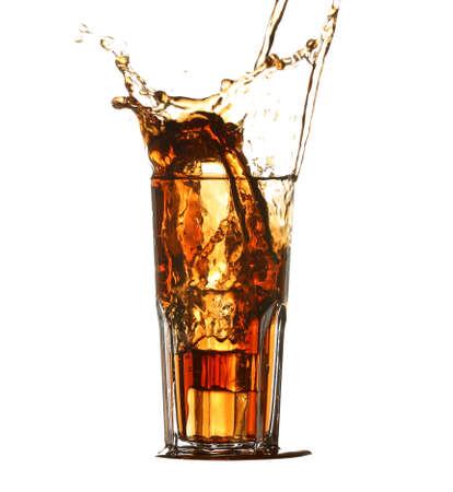 Glass of cold cola with splash on white background Foto de archivo