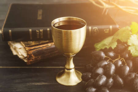 Chalice of wine with Holy Bible on dark wooden background