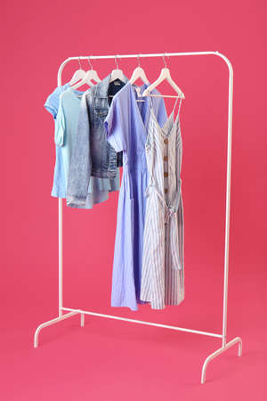 Rack with hanging clothes on color background Stockfoto