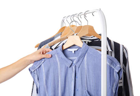 Woman choosing clothes hanging on rack against white background Stockfoto