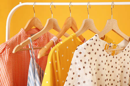 Rack with hanging clothes on color background, closeup
