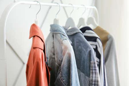 Rack with hanging clothes indoors, closeup