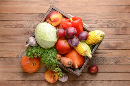 Box with many healthy vegetables and fruits on wooden background Stockfoto
