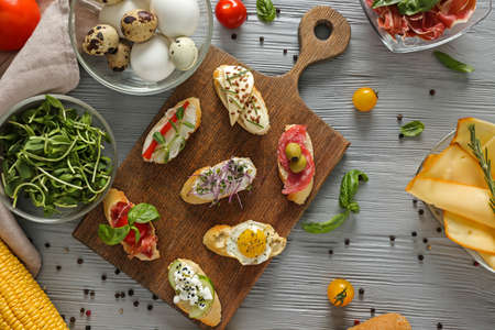 Board with different tasty sandwiches on wooden table Foto de archivo