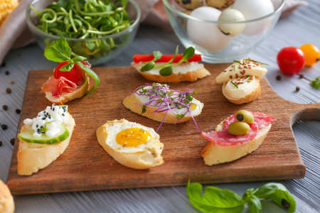 Different tasty sandwiches on wooden board