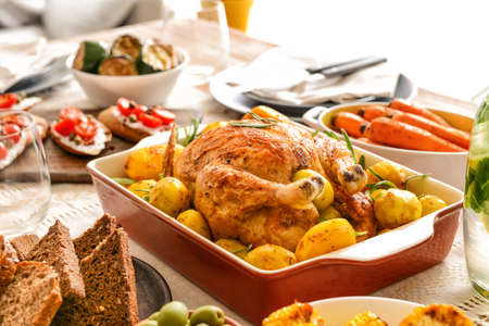Baking dish with tasty chicken and potato on served table Stock fotó