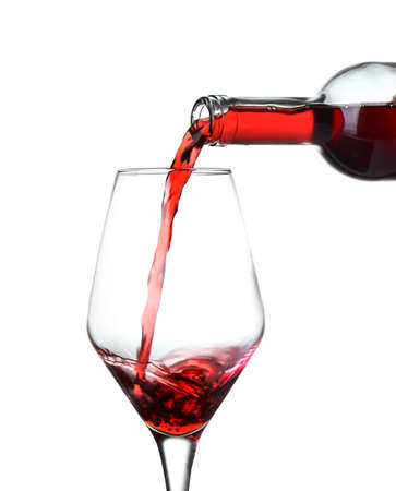 Pouring of wine into glass on white background