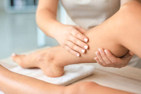 Beautiful young woman receiving foot massage in spa salon