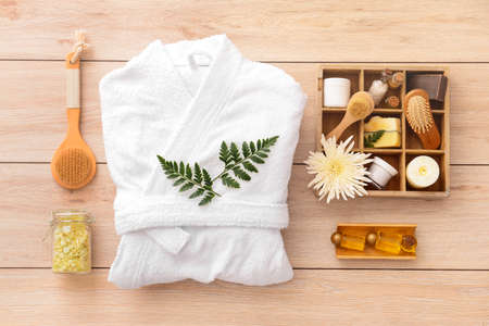 Bathrobe and set of spa items on wooden background