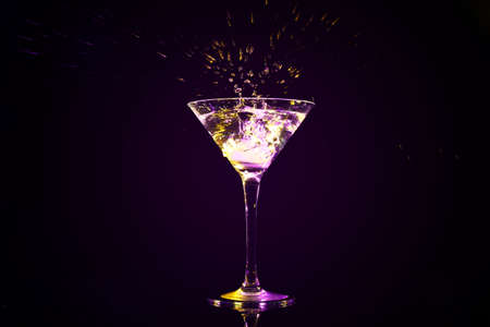 Dropping of ice cube into glass with tasty cocktail on dark background