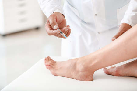 Doctor giving young woman with joint pain injection in clinic, closeup
