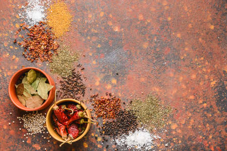 Bowls with different spices on color background