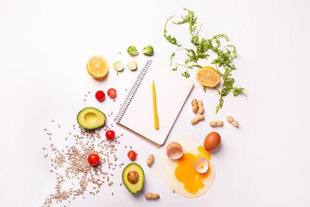 白い背景に健康な製品を持つノートブック。ダイエットの概念 写真素材