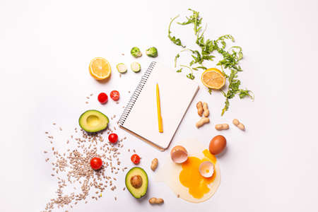 Notebook with healthy products on white background. Diet concept Stockfoto