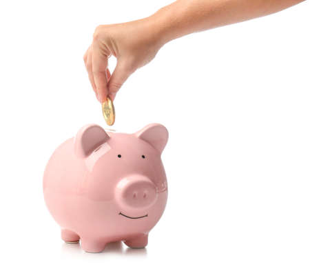 Female hand with coin and piggy bank on white background