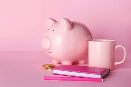 Piggy bank with stationery and cup on color background