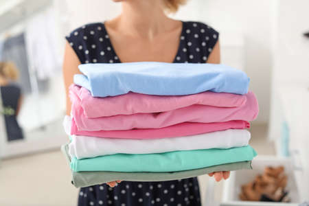 Woman with stack of clean clothes at home, closeup