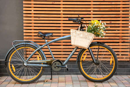 Modern bicycle with bag and bouquet of flowers on city street