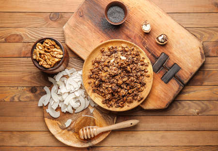 Tasty granola with coconut, honey and nuts on wooden table