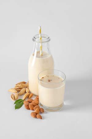 Tasty almond milk on white background