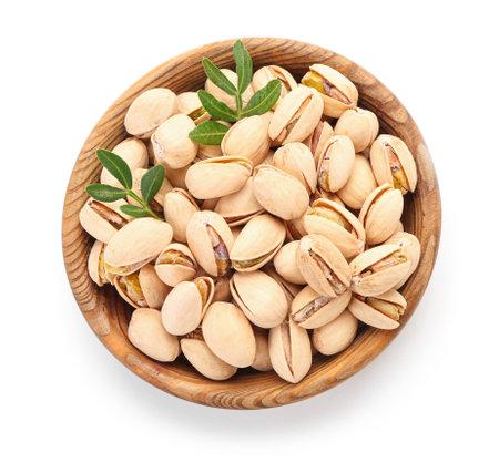 Bowl with tasty pistachio nuts on white background Standard-Bild