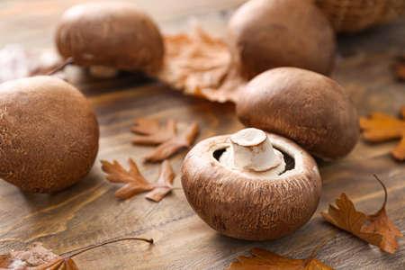 Fresh champignon mushrooms and autumn leaves on table