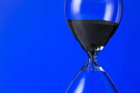 Crystal hourglass on color background Reklamní fotografie