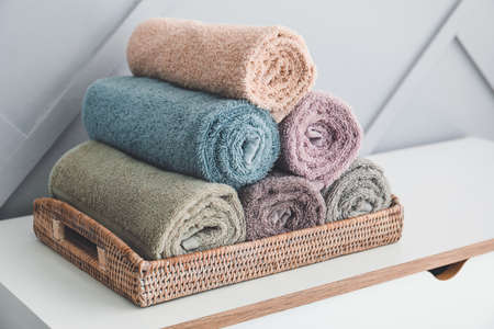 Clean towels on table near light wall