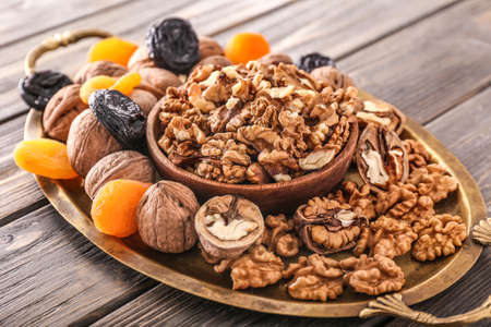 Tray with tasty walnuts and dried fruits on wooden background Stock Photo