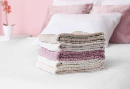 Stack of soft clean towels on bed