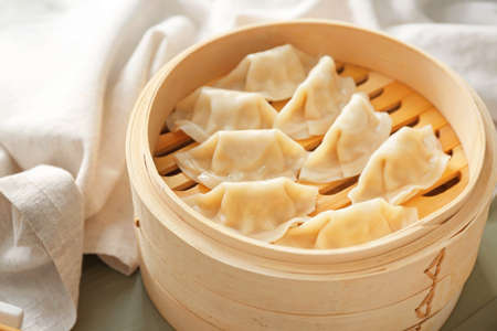 Bamboo steamer with tasty Japanese gyoza on table