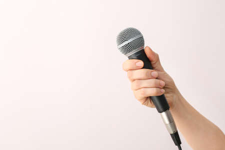 Female hand with microphone on light background