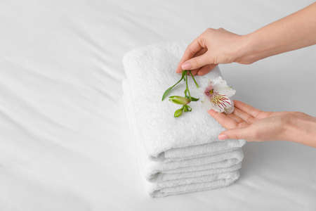 Woman putting flower on stack of clean towels on bed Imagens