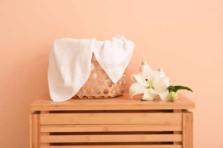 Basket with soft clean towels on wooden box near color wall Imagens