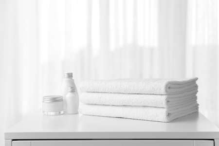 Soft clean towels and cosmetics on table near window