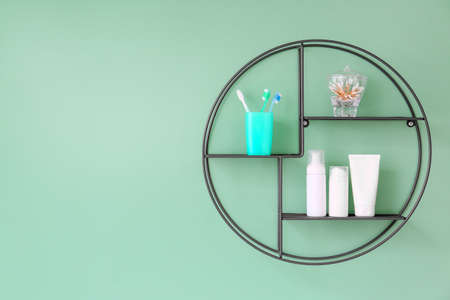 Shelf with bath supplies hanging on color wall