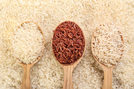 Spoons with different raw rice, top view
