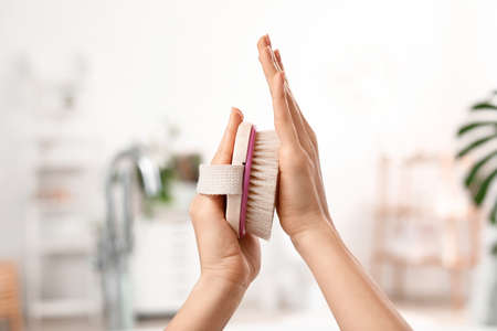 Hands of young woman with massage brush in bathroom Foto de archivo