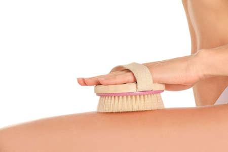 Beautiful young woman with massage brush on white background, closeup
