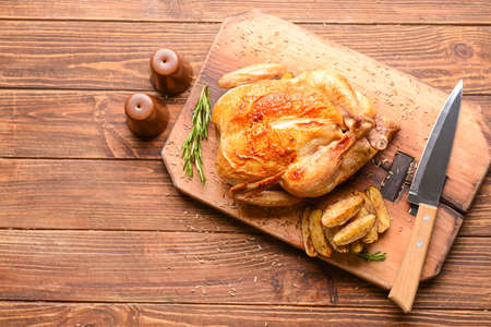 Board with baked chicken and potato on wooden table Archivio Fotografico