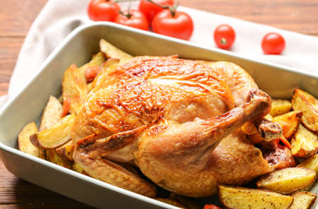 Dish with baked chicken and potato on wooden table