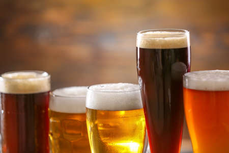 Glasses of different tasty beer on blurred background