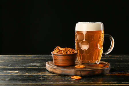Mug of fresh beer and snack on wooden table