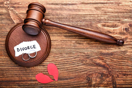 Judge's gavel, broken heart and rings on wooden background. Concept of divorce