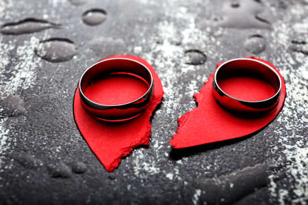 Broken heart and rings on grunge background. Concept of divorce